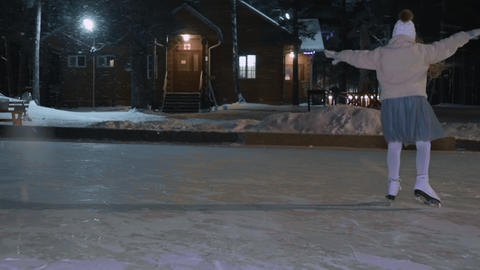 Happy girl skating on skates on winter ice rink while snowfall in night park Live Action