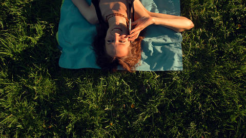Attractive sexy handsome red hair young woman lying on grass and calling on Live Action
