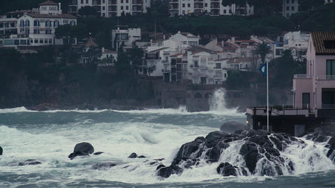 Storm waves hit the rocks in a small bay with a small coastal village. Dramatic Live Action
