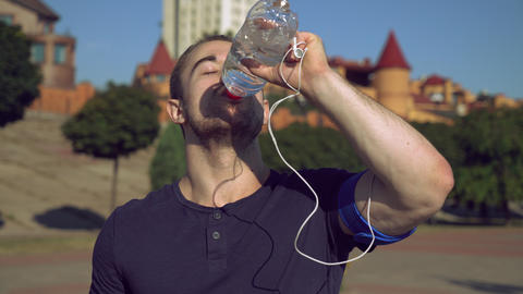 Guy enjoy drink after exercises outdoors Footage