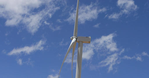 Windmill turbine turns side view beautiful cloud sky 4K Footage