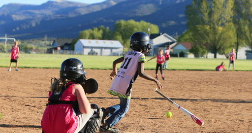Young girls playing softball rural park slow DCI 4K
