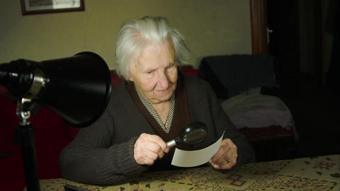 99 Years Old Woman Looking At An Old Photo With Magnifying Glass, Old Age Footage