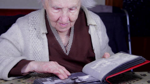 99 Years Old Woman Putting Photos In An Old Photo Album, Memories, Senescence Live Action