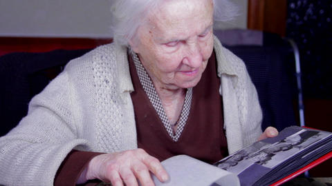 99 Years Old Woman Sitting At Table And Flipping Through An Old Photo Album Tilt Footage