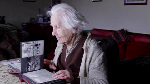 99 Years Old Woman Sitting At Table And Flipping Through An Old Photo Album, Pan Footage