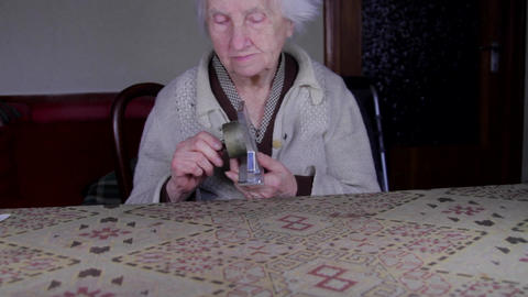 99 Years Old Woman Setting An Old Alarm Clock, Very Old Lonely Woman, Tilt Up Footage