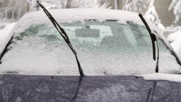 Frozen Car Windshield With Windshields Wipers Up in Blizzard, Tilt Up Footage