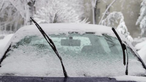 Frozen Car Windshield With Windshields Wipers Up in Blizzard, Tilt Down Footage
