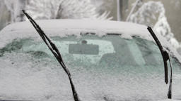 Frozen Car Windshield With Windshields Wipers Up in Blizzard, Pan Footage