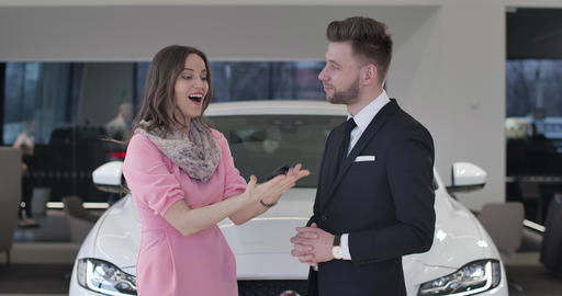 Portrait of excited Caucasian female customer buying automobile in car Live Action