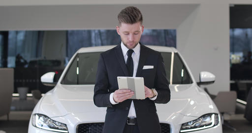 Succesful young car dealer standing in front of white automobile with tablet Live Action