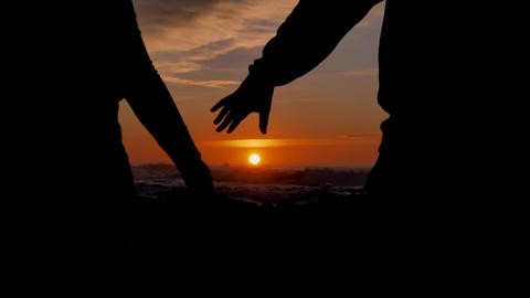 Slow motion couple joining hands together with sunlight in background. The sun's Live Action