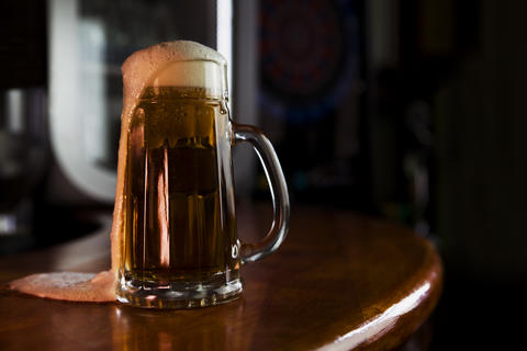 Beer in a Mug with Foam Resting on a Wooden Surface with Blank Space for a Logo or Text Fotografía