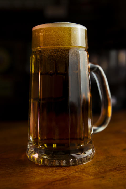 Beer in a Mug with Foam Resting on a Wooden Surface Fotografía
