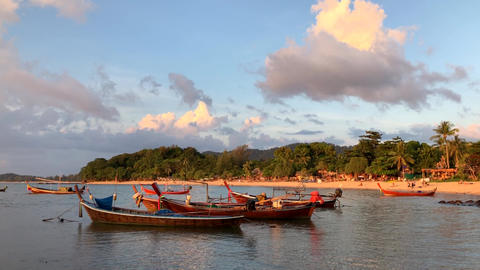 Picturesque sunset with traditional long tail boats on the beach in Koh Lanta Live Action