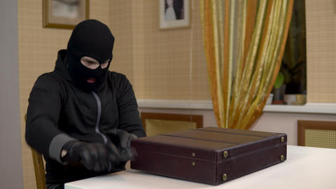 The robber is trying to open the suitcase. A masked thug opens a suitcase and Live Action