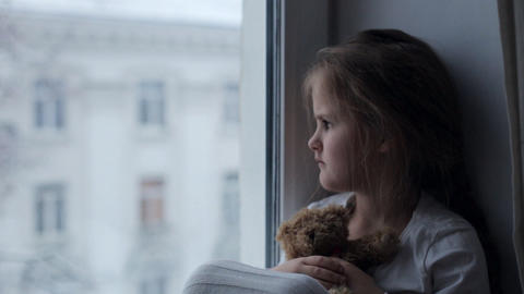 Beautiful sad little girl with her bear is sitting on the windowsill Live Action