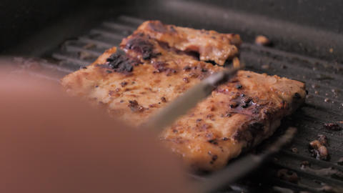 Close-up shot cooking and grill pork steak in the hot pan, select focus shallow depth of field GIF