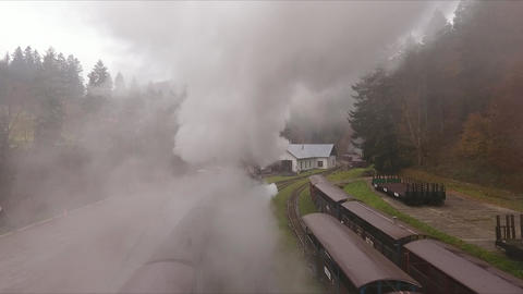 Aerial view through the smoke of the old train on the railway station in the mountains Live Action
