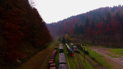 Panoramic drone shot in the mountains over a railway station, colorful autumn forest Acción en vivo