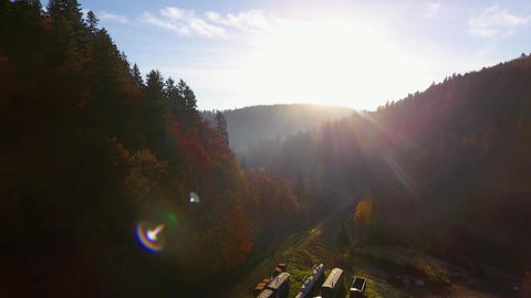Beautiful mountains at sunset, autumn forest valley panoramic view from drone, over railway station Acción en vivo