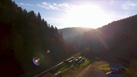 Beautiful drone shot of the sunset in the mountains, over a railway station Live Action