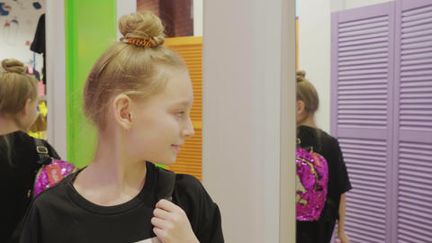 Teenager girl trying fashion backpack front mirror in fashion boutique at Live Action