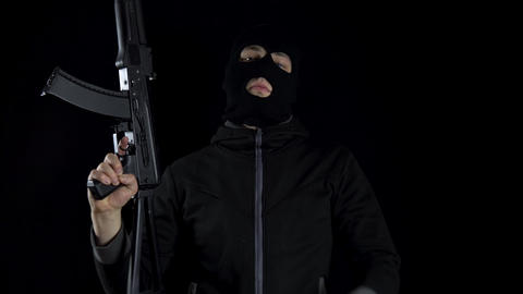 A man in a balaclava mask stands with an AK-47 assault rifle. The bandit stands Live Action