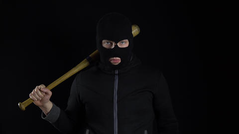 A man in a balaclava mask is standing with a baseball bat. A bandit stands on a Live Action
