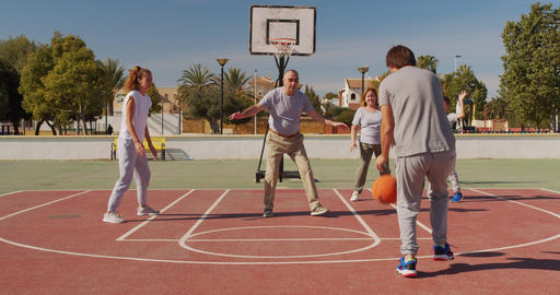 Multigeneration family playing basketball on outdoor court Live Action