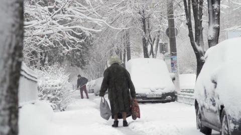 Old Woman Walking Slow On A Narrow Path In Snow, City Street, Blizzard, Winter Footage