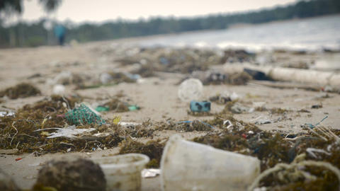 Plastic trash and waste litter an empty beach - handheld tilt up Footage