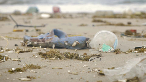 Pan revealing a large amount of plastic trash with live shells littering the bea Footage