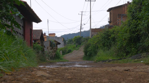 A dirt road in rural Mexico with newer nice homes and electric wires shot from t Footage