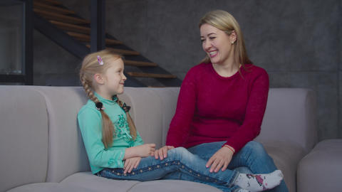 Caring mom and girl sharing on sofa during leisure Live Action