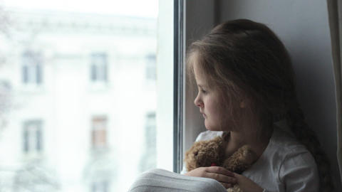 The child looks out the window in anticipation of his parents Live Action