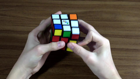 Top view of boys hands solving Rubik's Cube originally called Magic Cube Live Action