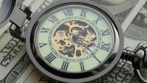 Pocket watch on the background of dollar bills. Close-up Live Action