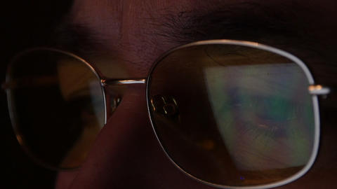 A man in glasses looks at the computer screen. The screen is reflected in the glasses Live Action