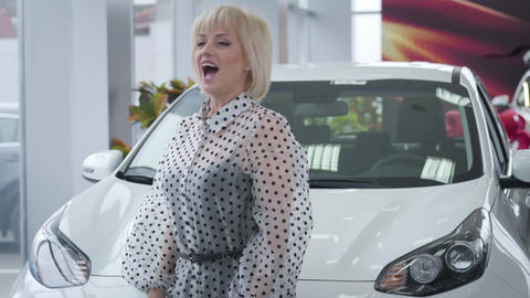 Cheerful mature Caucasian woman dancing with car keys in front of new vehicle Live Action