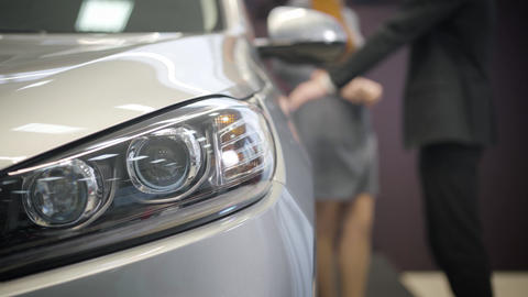 Close-up of car headlamp. Blurred Caucasian man opening door at the background Live Action