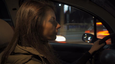 Driving a car at night - pretty, young woman driving her modern car at night, in Live Action