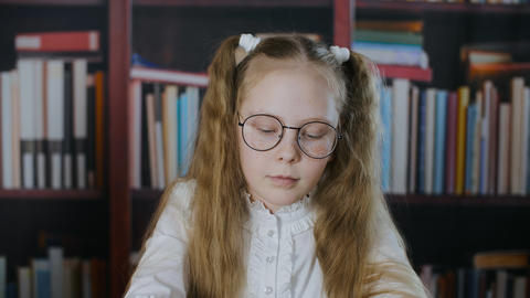 Portrait schoolgirl in round spectacles with two hair tail on bookshelf Live Action