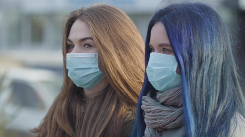 Side view close-up of two anxious women in protective masks looking away. Women Live Action