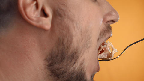 Close-up of a man with a beard who eats caesar salad from a fork. Caesar salad Live Action