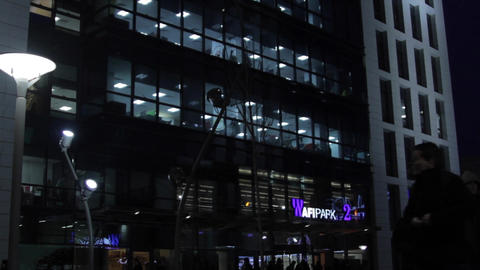 Business Center With Illuminated Offices, People Working, Night, Wintertime, Pan Footage