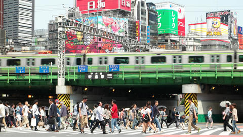 Tokyo- May 2016: People on crosswalk with colorful billboards in background, tra Footage