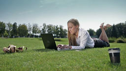 Businesswoman lying on green grass with laptop Footage