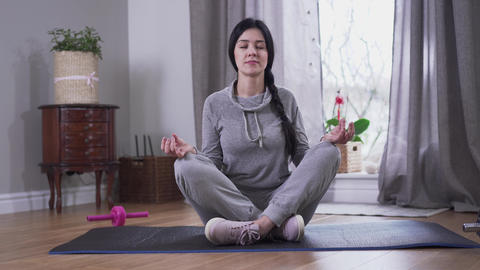 Calm brunette Caucasian woman sitting with eyes closed on yoga mat. Young woman Live Action
